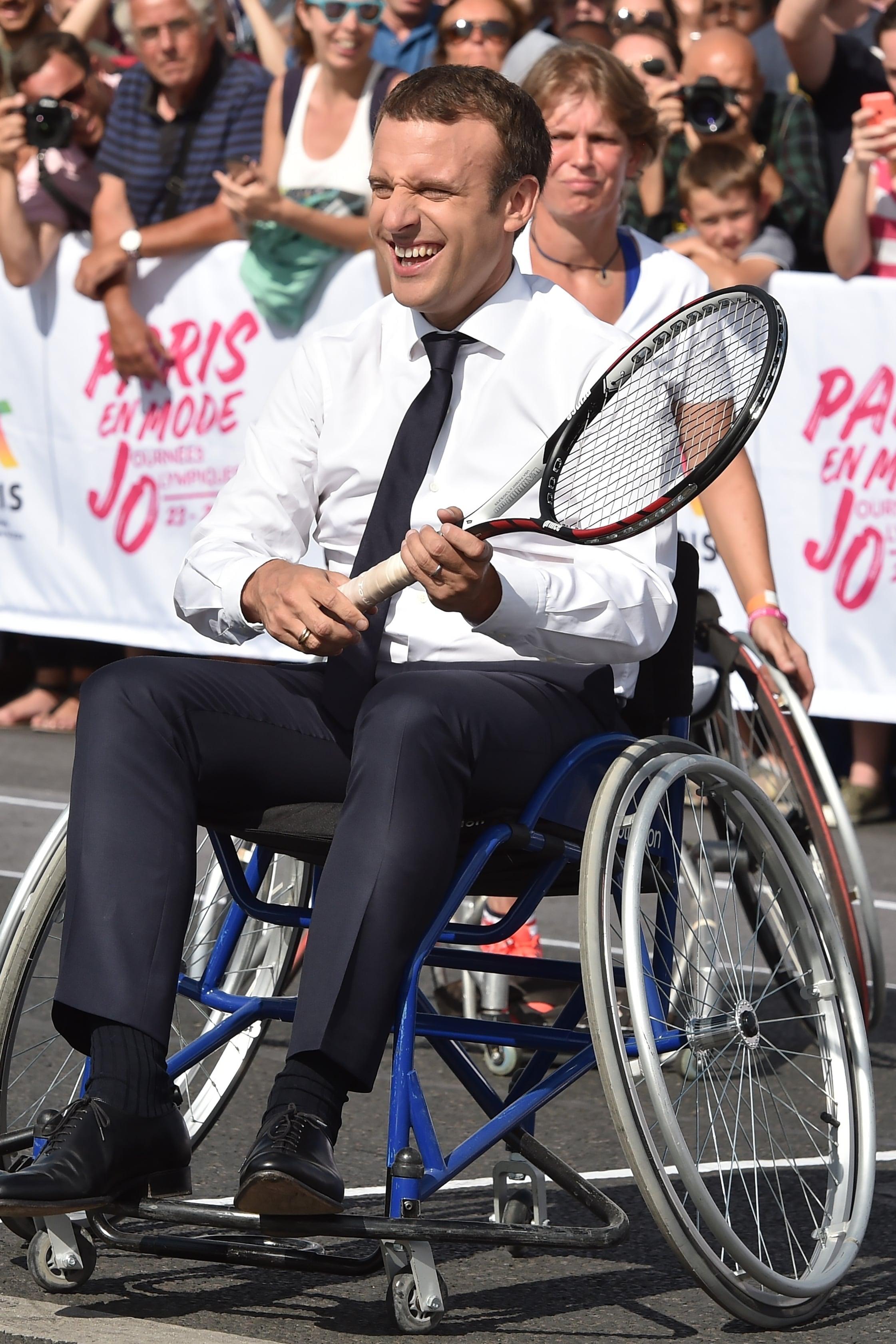 Photo d'Emmanuel Macron en fauteuil roulant manuel une raquette à la main qui joue au tennis avec des athlètes handicapés.